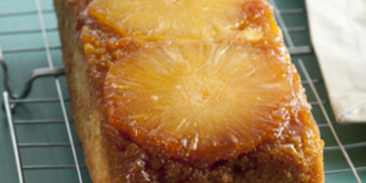 Foto em tons de azul e pardo, contém uma grade cinza com a torta com rodelas de abacaxi para decorar