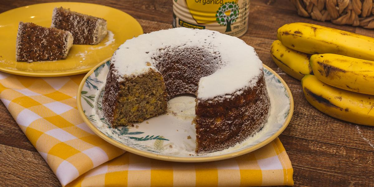 Fotografia em tons de amarelo e marrom de uma bancada de madeira com um pano xadrez amarelo e branco de um bolo de banana polvilhado com NINHO polvilhado. Ao fundo uma lata de NINHO, bananas e ovos.