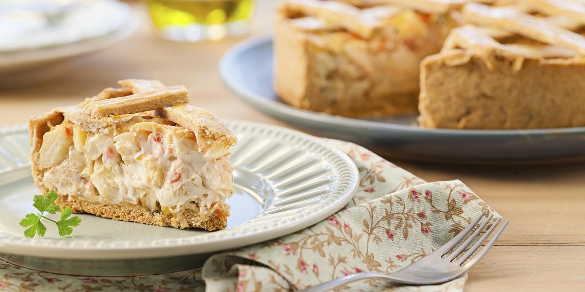 Fotografia em tons de bege em uma mesa de madeira com um pano florido em bege e vermelho e um prato branco apoiado nele com um pedaço de torta de palmito e alho-poró. Ao fundo, um prato grande com a torta cortada ao meio.