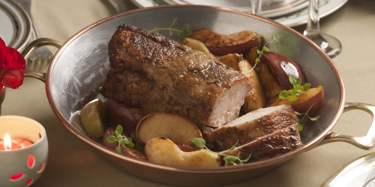 fotografia vista de cima de uma mesa, contém uma panela de inox com pedaços de carne dentro e pedaços de maçãs