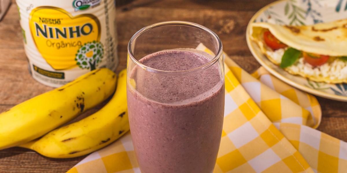 Fotografia em tons de amarelo de uma bancada com um pano xadrez amarelo e branco e um copo com a bebida de açaí. Ao fundo bananas, uma lata de NINHO e um prato com uma crepioca.