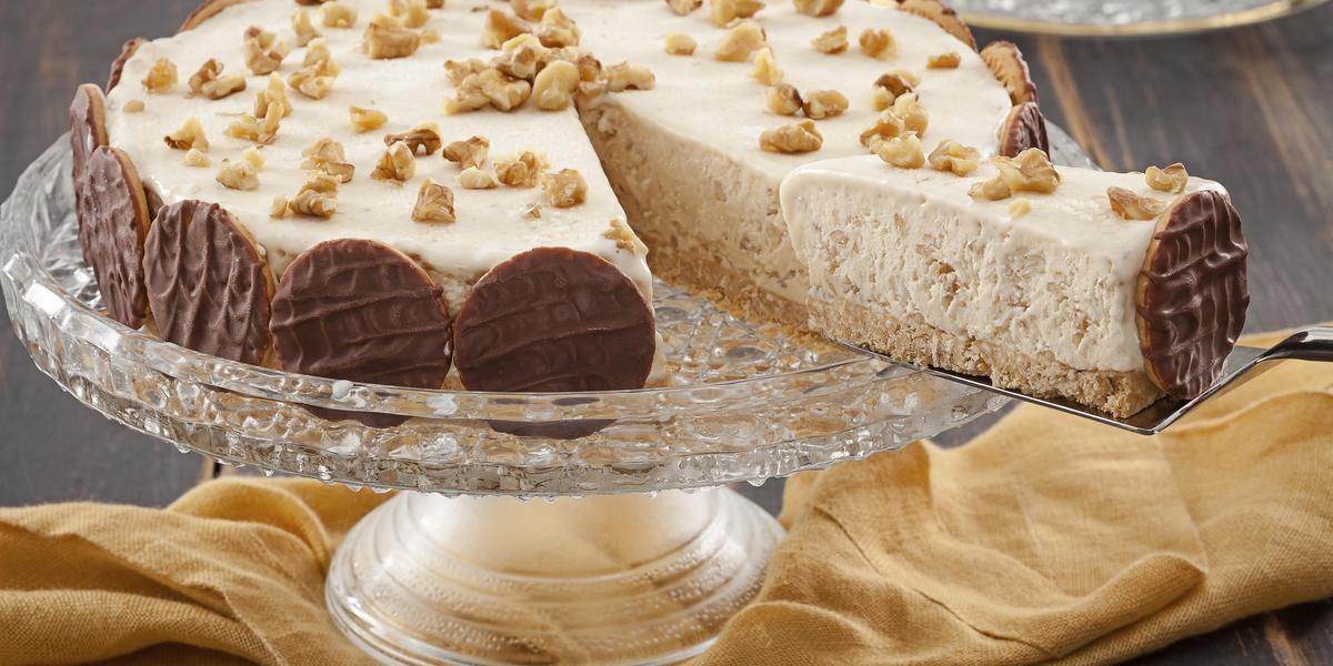 Fotografia em tons de marrom e amarelo de uma bancada de madeira com um paninho amarelo, sobre ele um prato de vidro com uma torta holandesa.