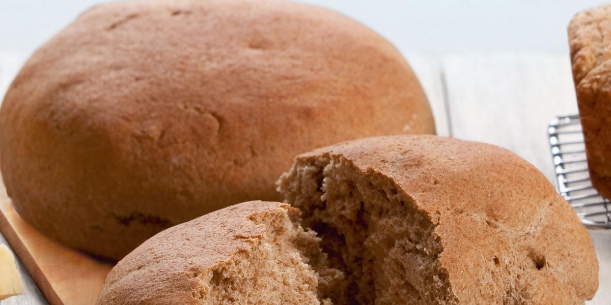 Fotografia em tons de marrom em uma bancada de madeira com uma tábua de madeira clara e o pão preto redondo grane apoiado nela, e um outro pedaço de pão já cortado.