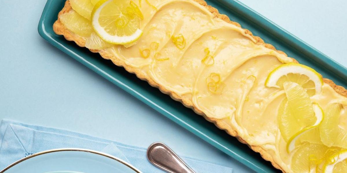 fotografia e tons de azul e amarelo tirada de cima de uma bandeja azul com a torta e rodelas de limão por cima