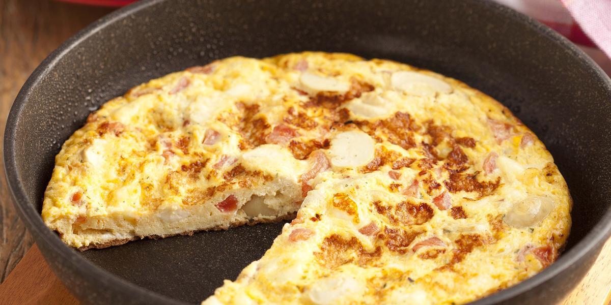Fotografia em tons de vermelho em uma bancada de madeira, uma tábua de madeira, um prato redondo fundo com a omelete dentro dele. Ao lado, pratos pequenos vermelhos com uma fatia da omelete.