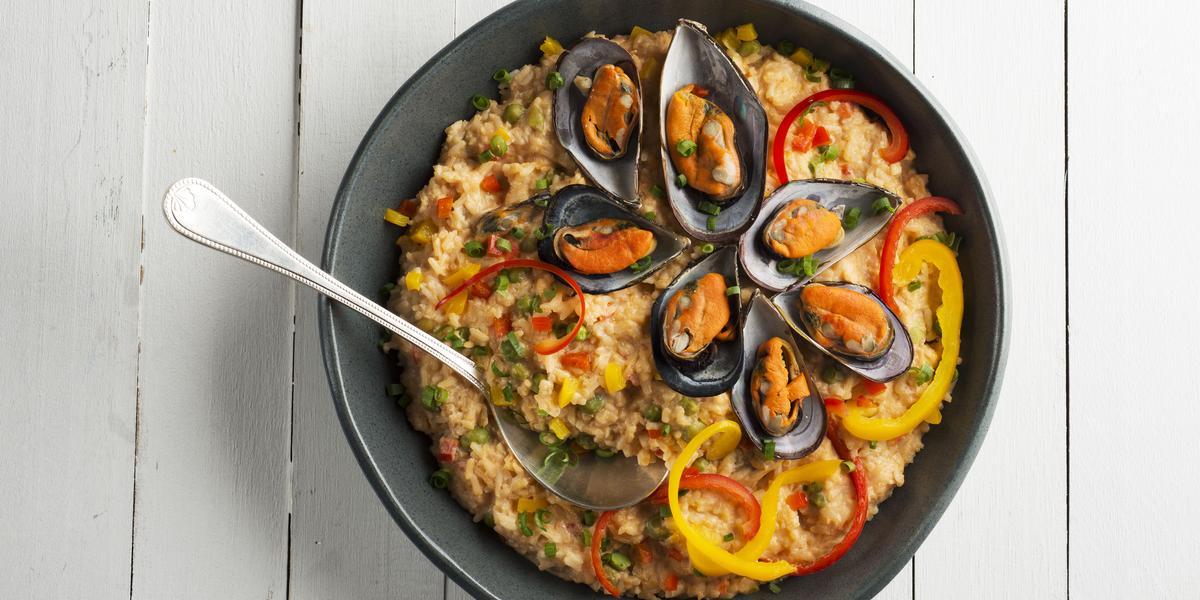 Fotografia em tons de branco e preto de uma bancada branca, sobre ele um prato preto com arroz com frutos do mar e uma colher.