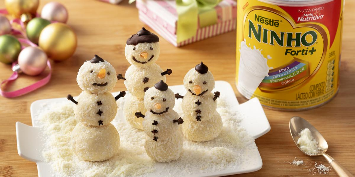 Fotografia em tons de marrom de uma bancada de madeira com uma tábua branca, sobre ela quatro bonecos de neve. Ao lado uma colher, uma lata de NINHO. Ao fundo bolinhas natalinas e caixinhas de presente.