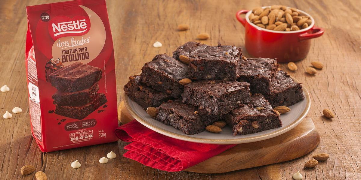 Fotografia em tons de marrom e vermelho de uma bancada de madeira com uma tábua de madeira e um paninho vemelho, sobre ele um prato redondo com pedaços de brownie. Ao fundo um recipiente redondo com amêndoas e um pacote de brownie dois frades.