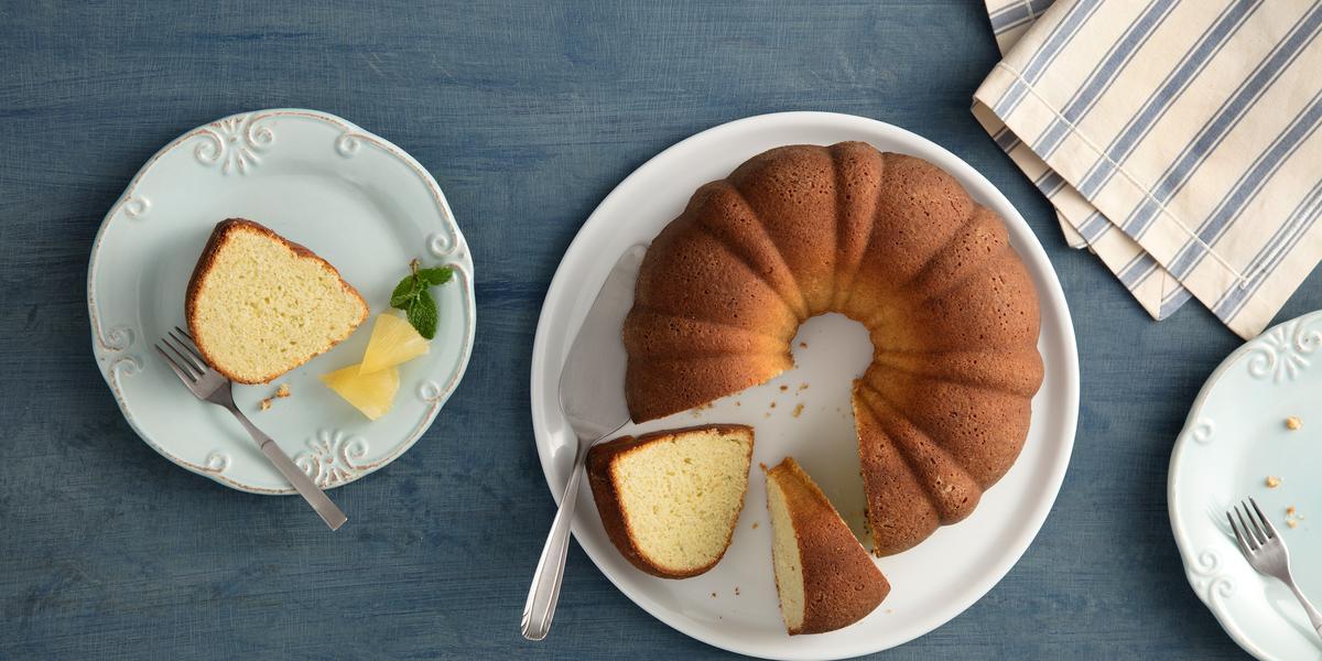 Fotografia em tons de branco, marrom e azul, em bancada azul vista de cima, com prato branco ao centro com bolo fatiado e uma espátula, no entorno prato com pedaço de bolo e um garfo, prato vazio com um garfo e guardanapo branco com listras azuis.