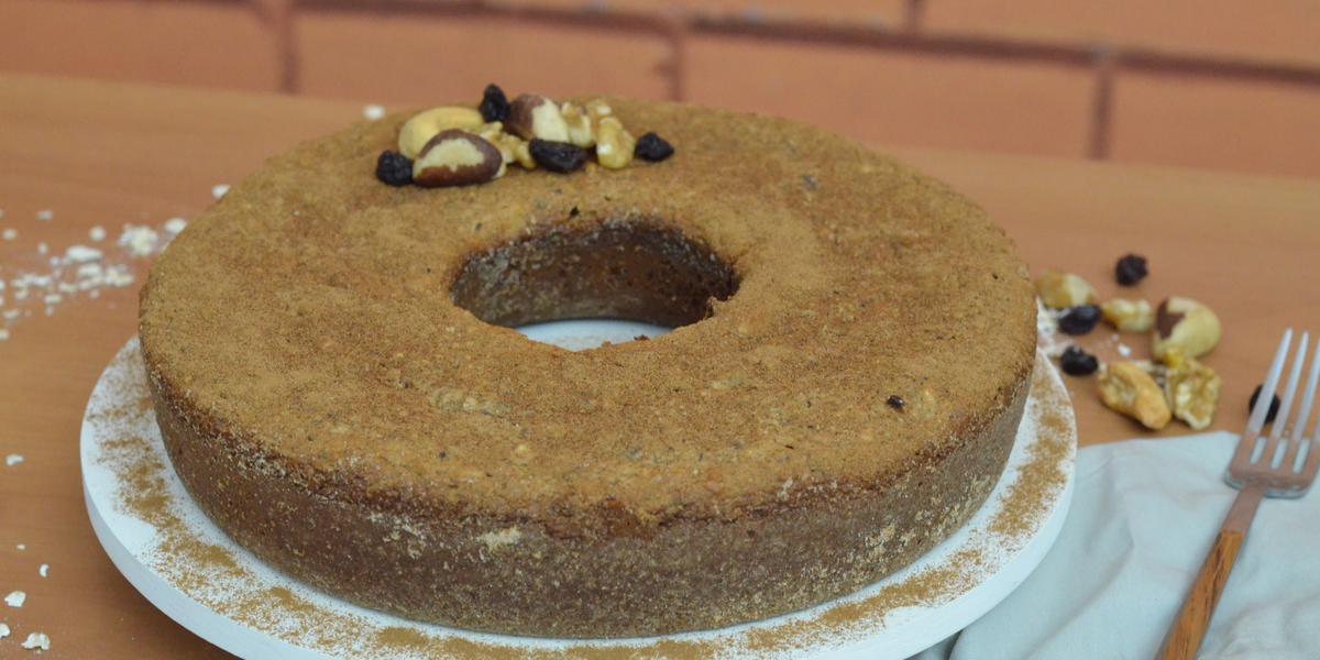 Fotografia em tons de marrom de uma bancada de madeira com um prato branco redondo, sobre ele um bolo de nozes. Ao lado um paninho branco com garfo e nozes.
