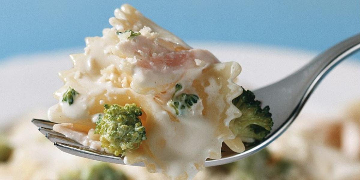 Fotografia em tons de azul, branco e verde, ao centro porção de macarrão com brócolis ao creme suspenso em um garfo, abaixo prato branco com macarrão, creme e brócolis, tudo sobre bancada azul.