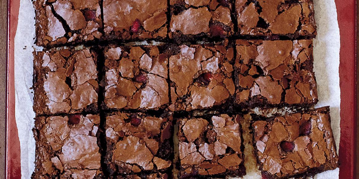 fotografia em tons de marrom e branco de uma bancada vista de cima, contém um pano branco e por cima pedaços quadrados de bolo de chocolate