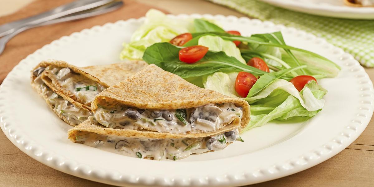 em um prato redondo e branco contém panquecas recheadas com cogumelos com creme e aso lado folhas com fatias de tomatinhos