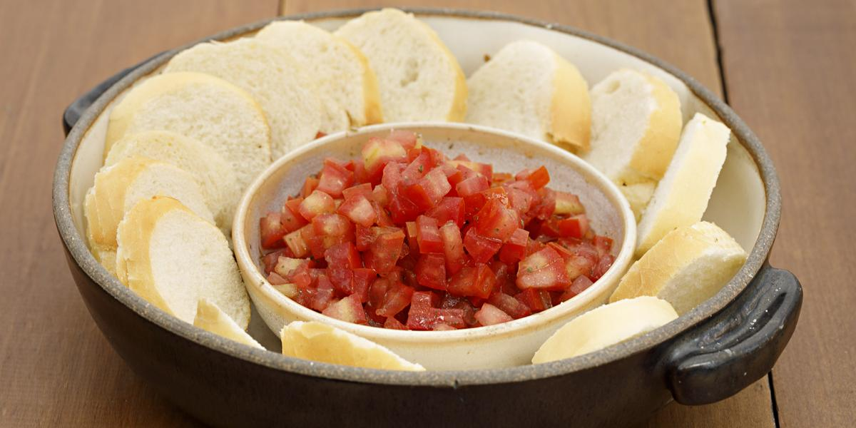 Fotografia em tons de vermelho em uma bancada de madeira com uma panela preta de ferro com alças laterais e vários pães fatiados com um potinho de molhinho de tomate.