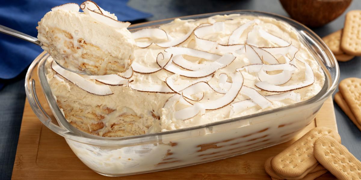 Fotografia em tons de branco, com tábua de madeira com um recipiente de vidro alto com o pavê de coco com biscoitos maisena São Luiz espalhados pela mesa.