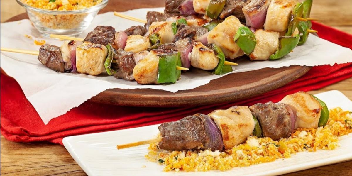Fotografia em tons de marrom em uma bancada de madeira com um pano vermelho, um prato marrom com espetinhos de carne e frango em cima dele. Ao fundo, um potinho de vidro com farofa.