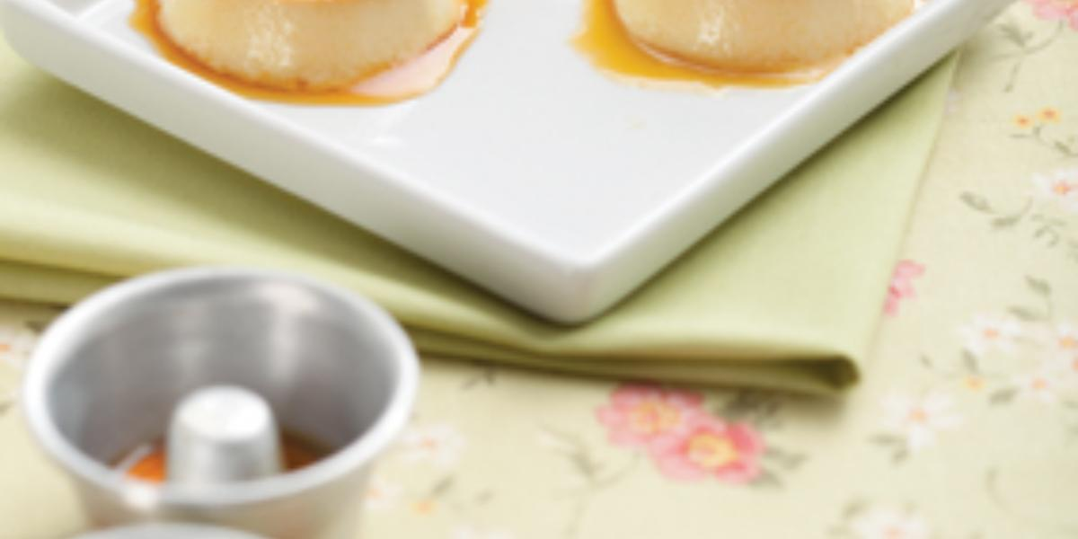 Fotografia em tons de verde e branco de uma bancada florida com um paninho verde, sobre ele um prato quadrado branco com três minipudins com calda. A frente três mini formas de pudim.