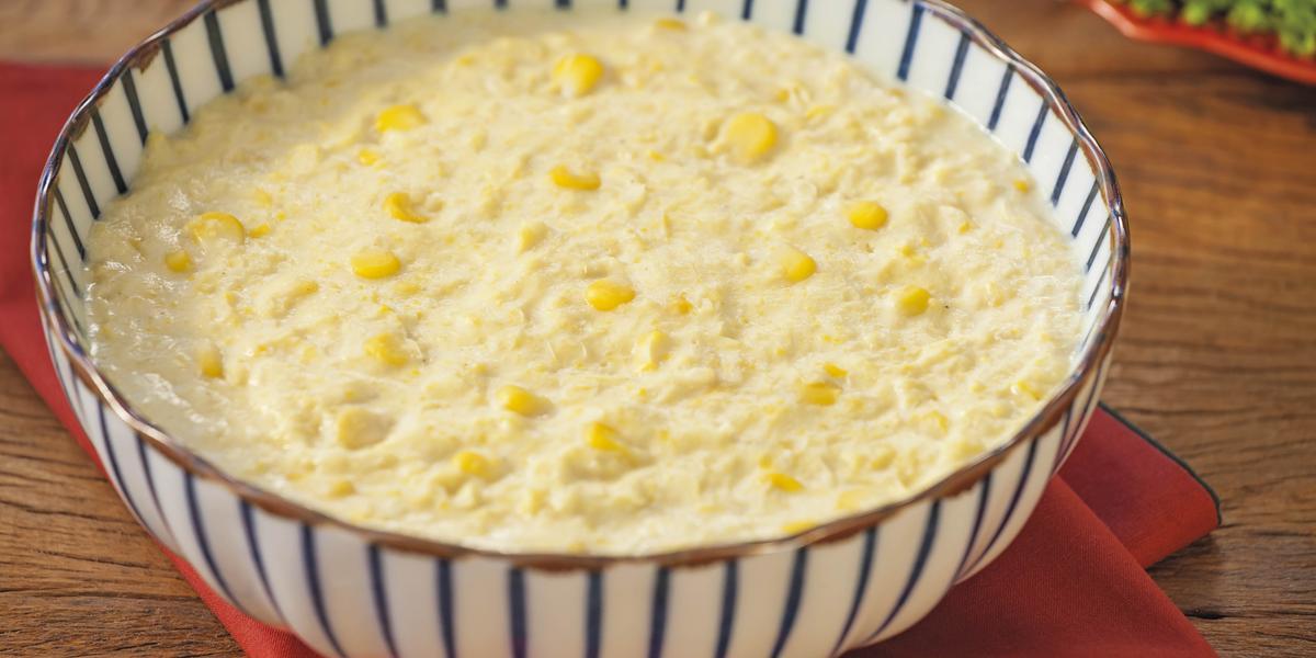 Fotografia em tons de branco e amarelo, ao centro sopeira branca listrada de azul com creme de milho , sobre guardanapo vermelho e bancada de madeira.