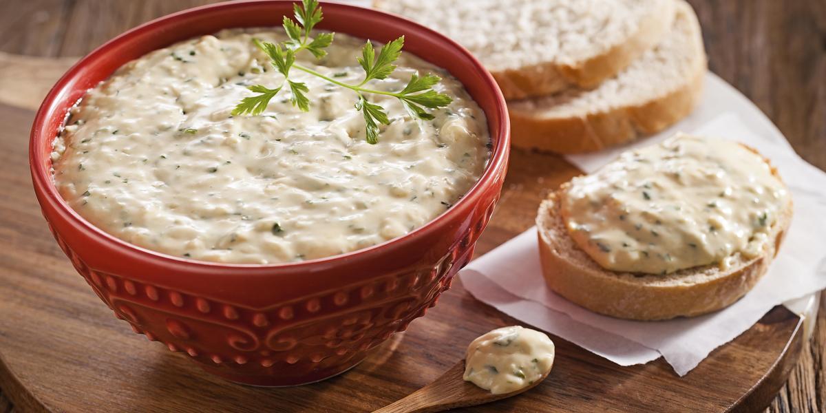 Fotografia de um bowl vermelho com o patê de queijo dentro, uma folhinha verde para decorar e ao lado pães fatiados com o patê em cima.