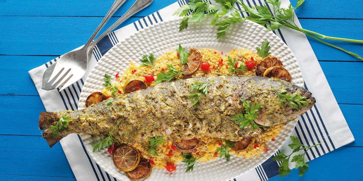 Fotografia em tons de azul e branco de uma bancada de madeira azul com um paninho branco e azul listrado, sobre ele um prato branco oval com um peixe assada e farofa. Ao fundo um garfo e um ramo de salsinha.
