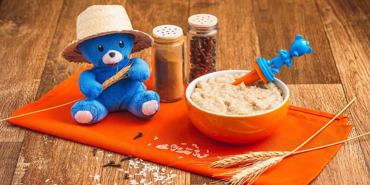 Fotografia em tons de laranja e azul de uma bancada de madeira com um paninho laranja e um pote laranja com a papinha. Na frente, grãos de arroz e cravos decorando e uma pelúcia azul com chapéu de palha.