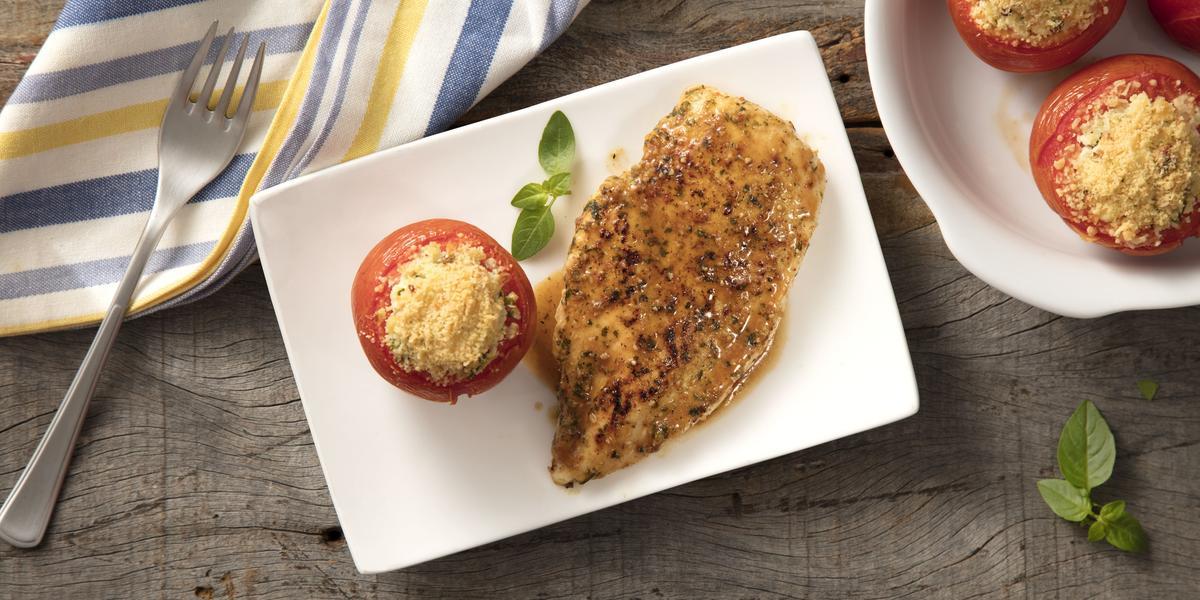 Fotografia em tons de branco, azul e cinza de uma bancada cinza vista de cima, um prato branco contém um filé de frango com um tomate e queijo por cima para decorar. Ao lado um recipiente branco redondo com 3 tomates e um pano listrado em azul e branco.