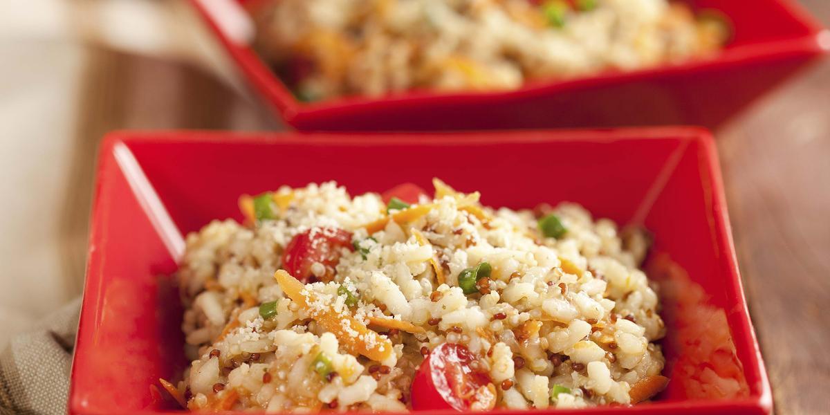 Fotografia em tons de vermelho, marrom e branco, com dois potinhos quadrados contendo um arroz colorido  e queijo ralado, ao lado guardanapo em tons de branco e marrom, tudo sobre bancada de madeira rústica.