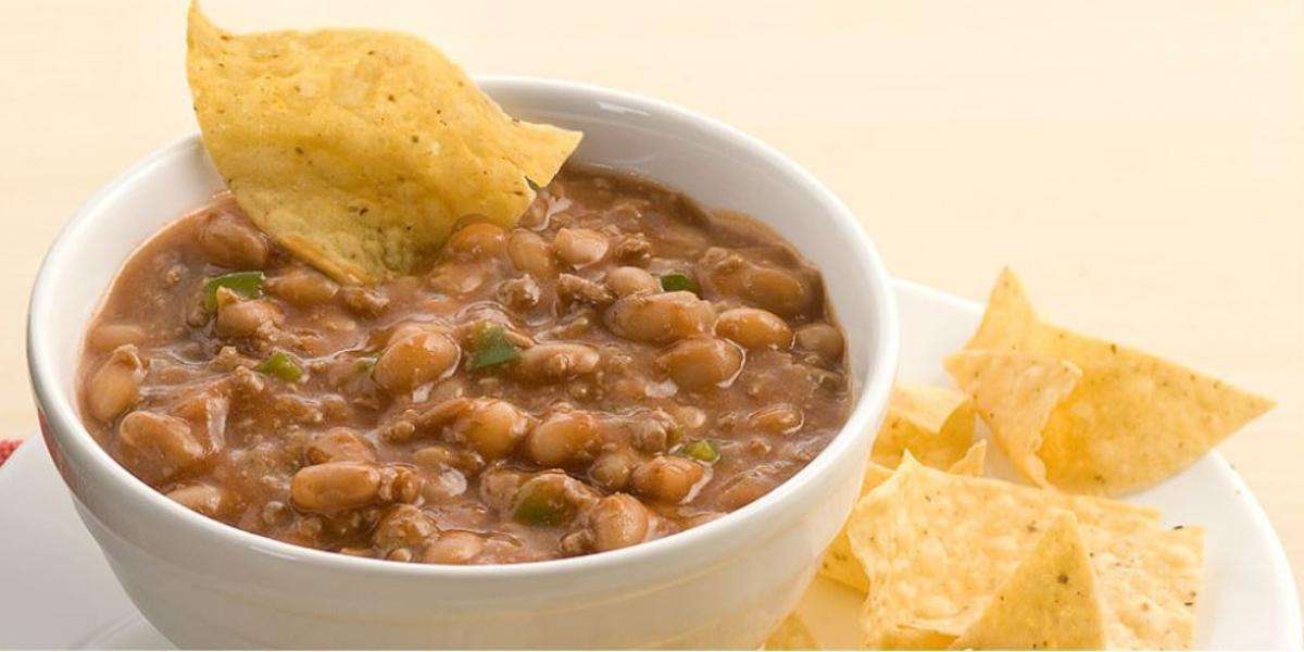 Fotografia de um bowl branco com chilli dentro, grãos de feijão da superfície e servido com tortilhas de milho ao lado no prato branco.
