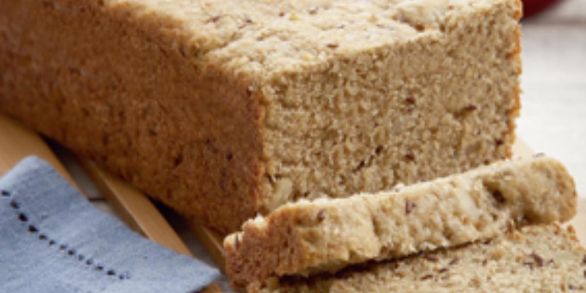 Fotografia em tons de branco e azul de uma bancada branca com uma tábua de madeira, sobre ela um pão com duas fatias cortadas. Ao lado um paninho azul. Ao fundo uma faca.