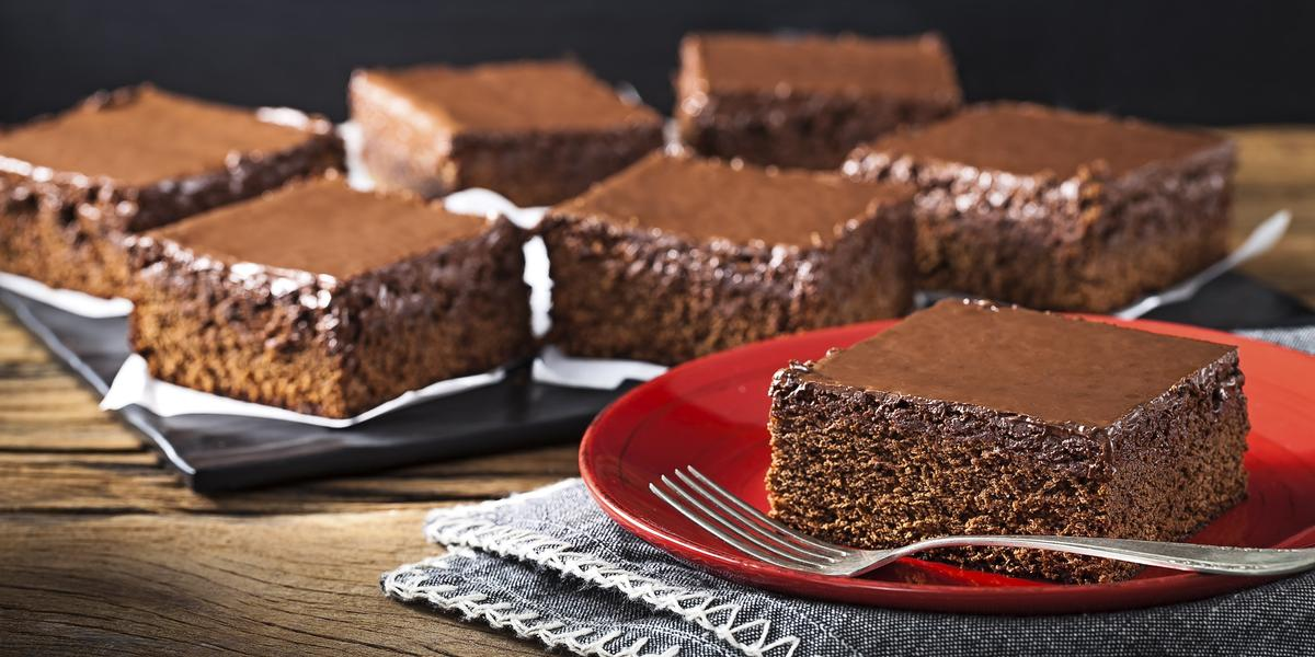 Fotografia em tons de marrom, vermelho e preto de uma bancada marrom escura e um paninho azul, sobre ele um prato vermelho redondo com um pedaço do bolo pão de mel. Ao fundo seis pedaços do bolo pão de mel sobre uma tabua preta com guardanapos.
