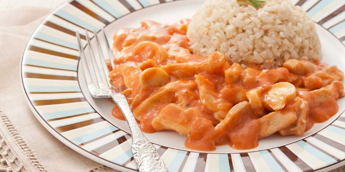 Fotografia em tons de marrom em uma bancada com uma toalha bege, um prato branco raso grande com detalhes listrados em azul e marrom, com o strogonoff de frango com molho e arroz integral.