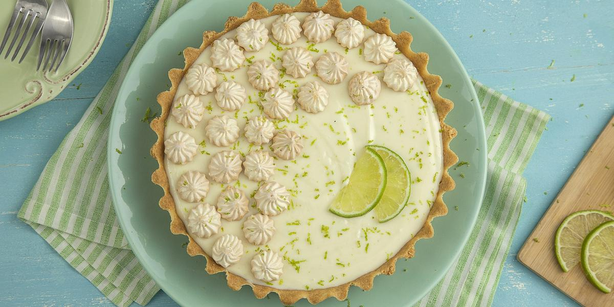 Fotografia em tons de verde e azul, ao centro torta de limão com suspiro, raspas e fatias de limão sobre prato verde e guardanapo listrado em verde, tábua com fatias de limão, no alto prato verde com dois garfos, tudo sobre bancada azul.