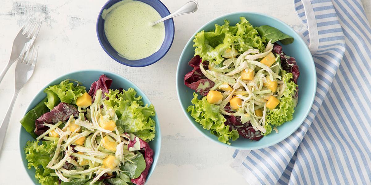 Fotografia em tons de branco, azul e verde de uma bancada branca vista de cima, contem dois potes azuis e redondos e ambos com saladas dentro. Ao lado um pano azul com branco, 2 garfos e um pote redondo azul com molho