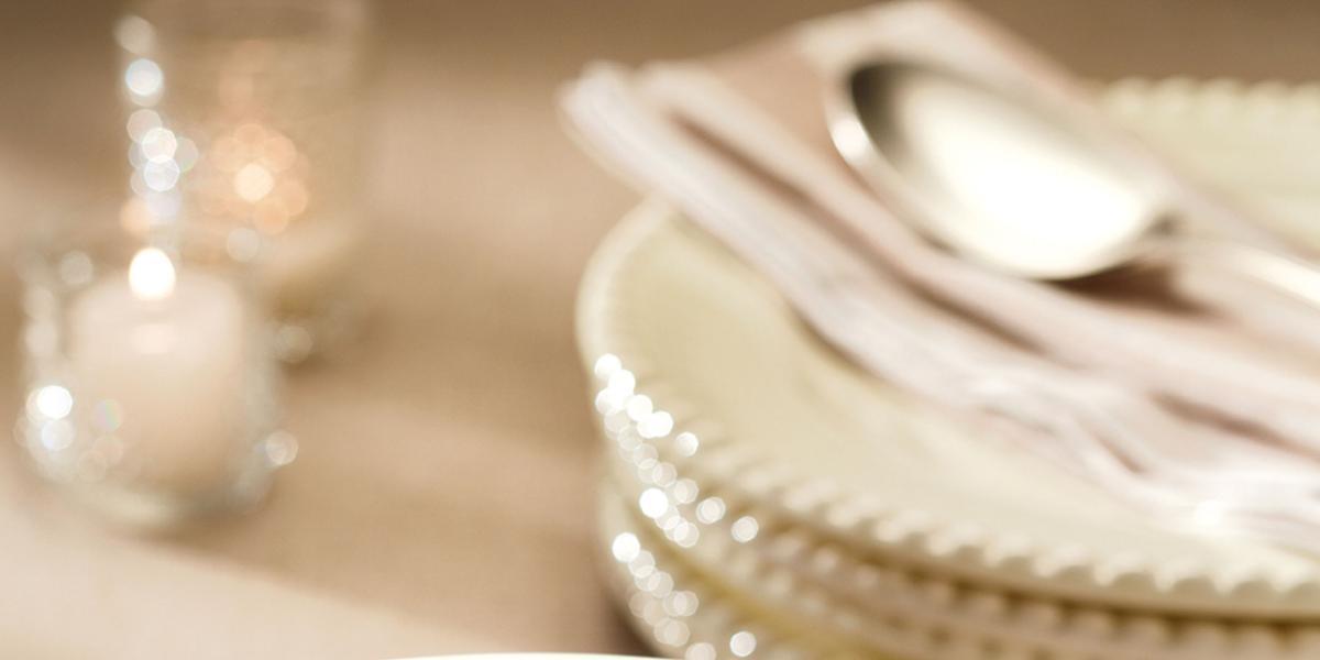 Fotografia em tons de prata e bege, com recipiente de inox com arroz cozido, amêndoas e limão-siciliano, ao fundo pratos empilhados com talheres por cima de um guardanapo, decoração com vela, um copo, tudo sobre bancada de cor bege.