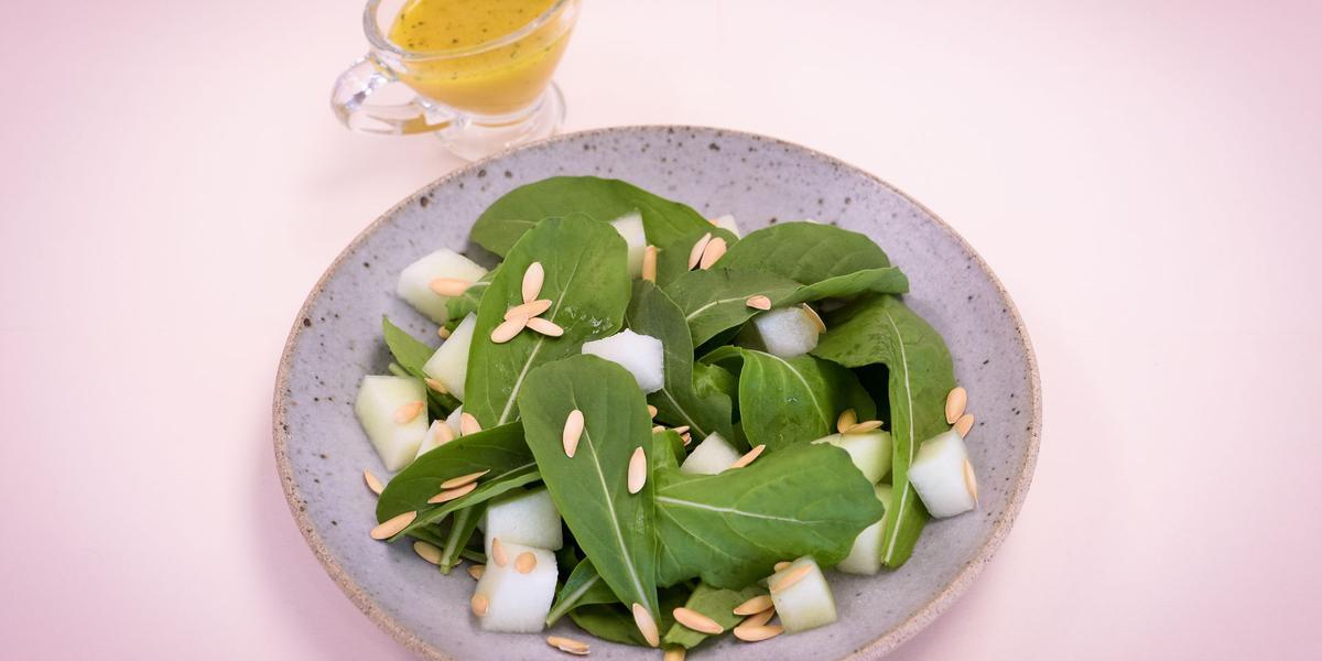 Fotografia em tons de rosa e verde em uma mesa de madeira rosa com um prato redondo raso lilás e a salada de rúcula com limão dentro dele. Ao fundo, um potinho com azeite.