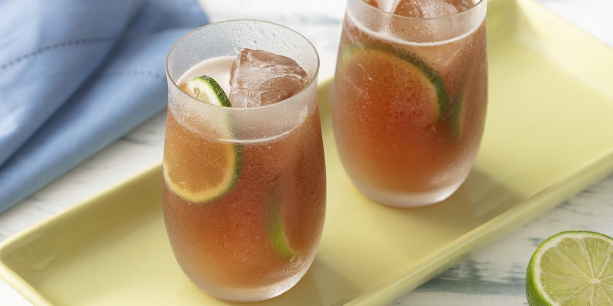 Fotografia em tons de azul e verde de uma bancada de madeira branca e um prato retangular verde, sobre ele dois copos de vidro com chá mate, gelo e limão. Ao fundo um paninho azul, a frente meio limão.