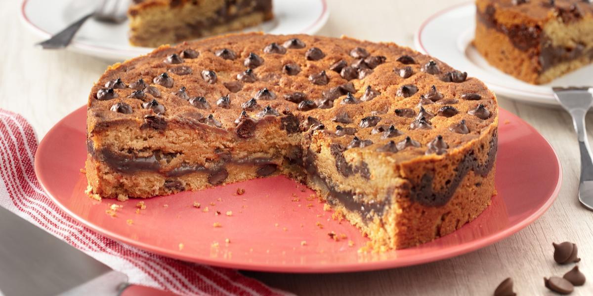 Fotografia em tons de branco e vermelho de uma bancada de madeira branca com um prato vermelho, sobre ela uma torta. Ao fundo dois pratos redondos com duas fatias de torta e dois garfos. A frente um paninho vermelho e branco com uma espátula.