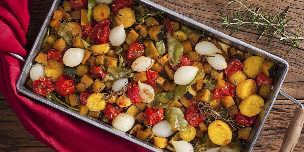 Fotografia de um recipiente de ferro com alças de madeira, dentro estão todos os legumes ficados em cubos assados, e ao lado está um guardanapo de tecido vermelho.