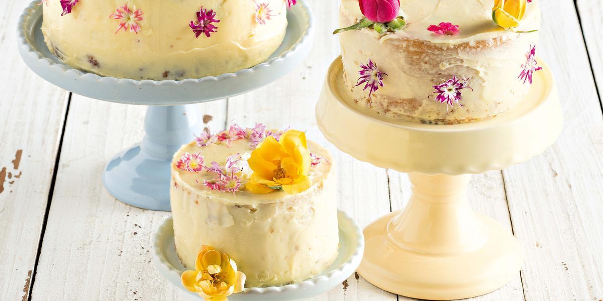 Fotografia em tons de branco, azul e pardo de uma bancada de madeira cinza vista de cima. 3 pratos para bolo em diferentes tamanhos com bolos encima e cada bolo é decorado com flores rosas e amarelas.
