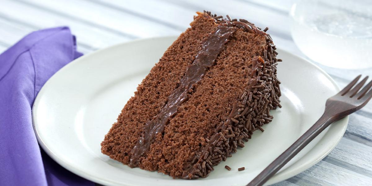 Foto de um prato branco numa mesa de madeira branca com uma fatia de bolo de chocolate dentro e um garfo do lado