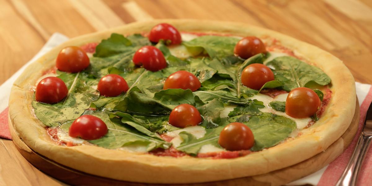 Fotografia em tons de dourado, verde e vermelho, ao centro pizza com folhas verdes e tomate-cereja sobre tábua redonda e guardanapo branco e vermelho, com talher ao lado, tudo sobre bancada de madeira em tons marrom.