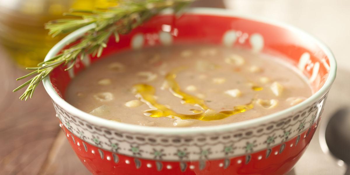 Fotografia em tons de vermelho em uma mesa de madeira com um recipiente redondo e fundo vermelho com a sopa de feijão dentro. Ao lado, um guardanapo de pano bege com uma colher apoiada nele e ao fundo, um potinho de azeite.