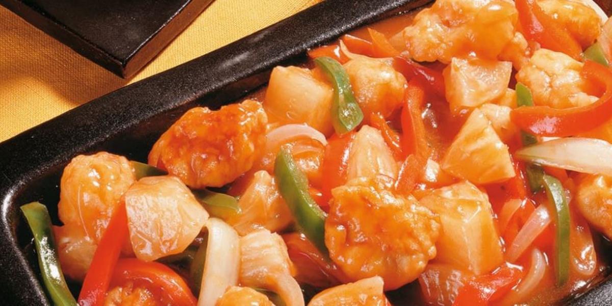 Fotografia em tons de vermelho em uma mesa de madeira e uma travessa preta retangular com o frango agridoce à moda cantonesa dentro.
