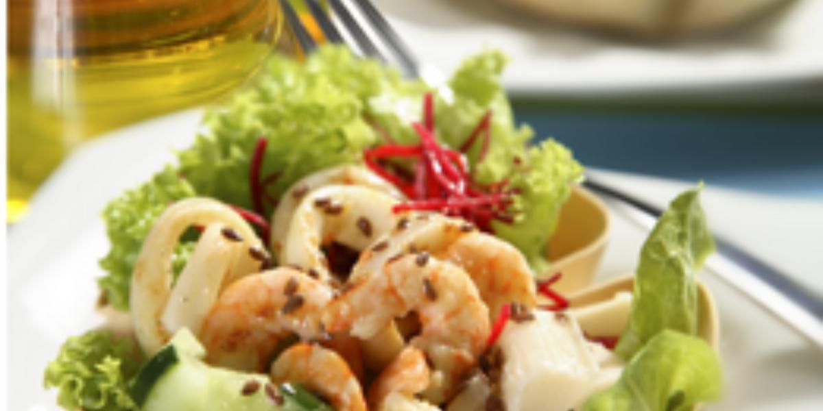 Fotografia em tons de verde em uma mesa com um vidro de azeite, um prato branco raso, um recipiente branco em formato de concha com a salada de alface, beterraba ralada, cenoura ralada e camarões dentro dele.