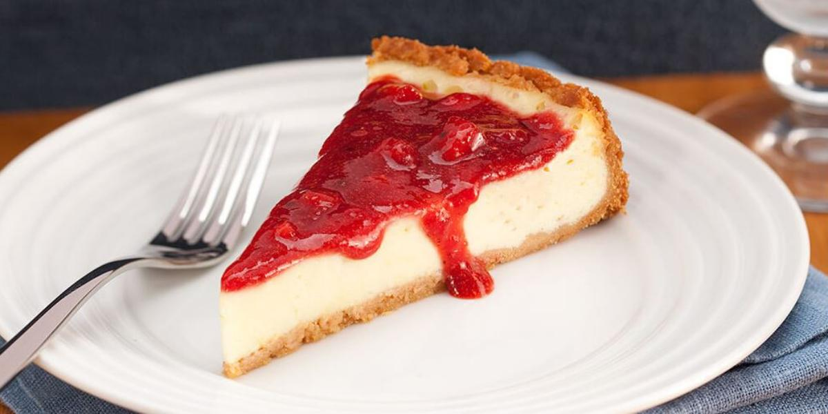Fotografia em tons de branco e vermelho, no centro na foto está uma fatia da torta coberta com geleia de morango, ao lado está um garfo e embaixo do prato um guardanapo azul.