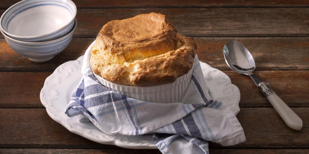 Fotografia em tons marrom de bancada de madeira, um prato com um pano listrado em azul por cima, no prato um pote com o suflê, do lado esquerdo uma colher e no direito dois potes brancos.