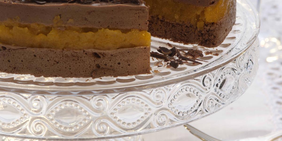 fotografia em tons de branco e marrom de uma bancada com panos branco, contém um suporte para servir sobremesas transparente com uma torta de mousse de chocolate com uma fatia retirada