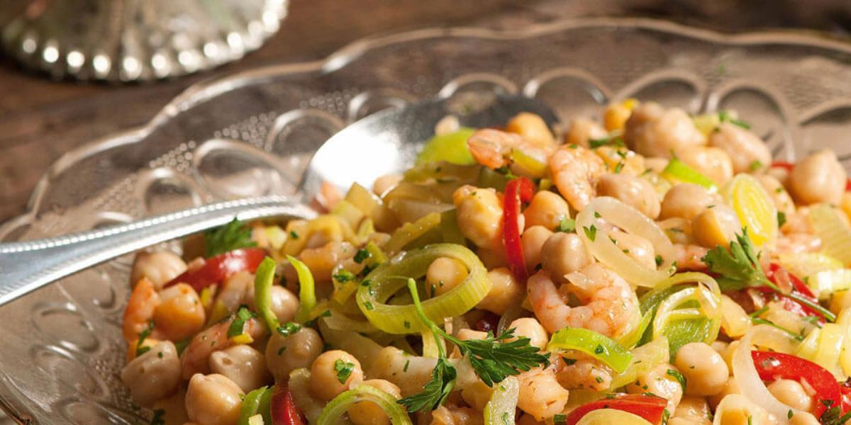 Fotografia em tons de bege e marrom, com salada de grã0-de-bico e legumes de cores verde e vermelha, dentro de saladeira de vidro com uma colher de servir, tudo sobre bancada de madeira.