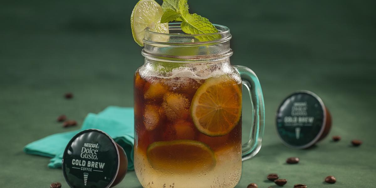 Fotografia em tons de verde de uma bancada verde, sobre ela um copo de vidro com cold brew e limões. Ao lado capsulas de Dolce Gusto Cold Brew e um paninho azul.