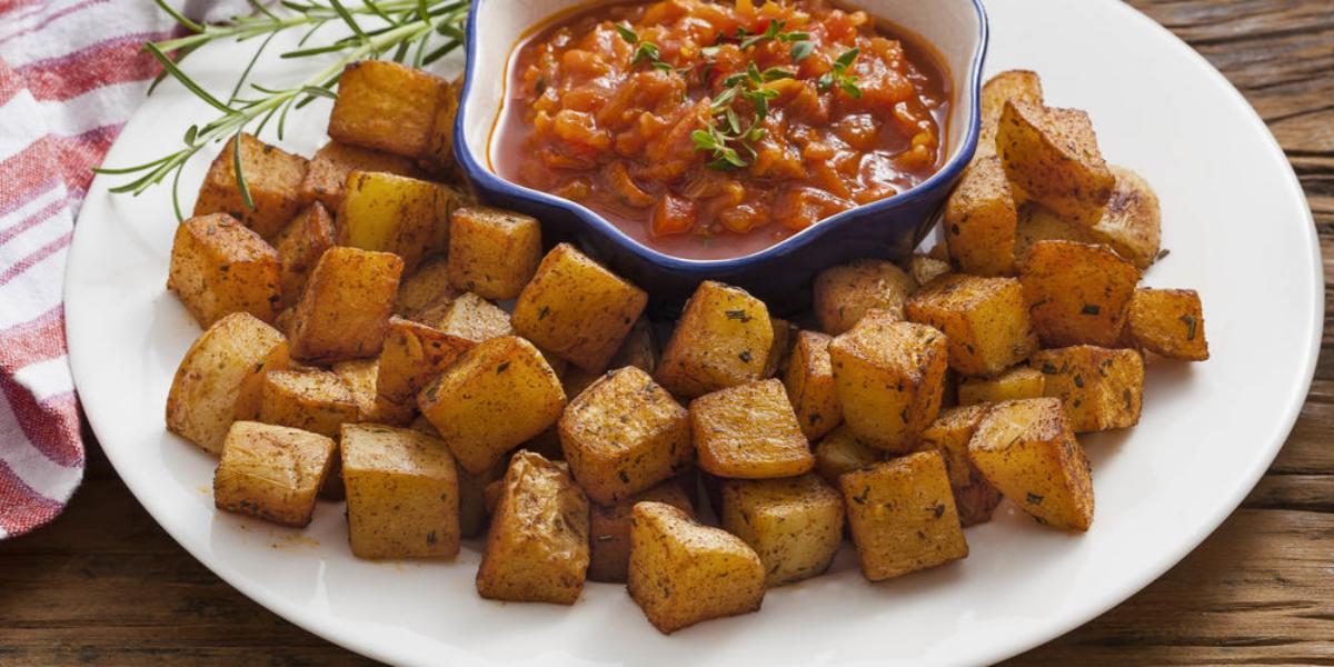 Fotografia em tons de vermelho em uma bancada de madeira escura com um pano branco com listras vermelhas e um prato branco raso grande ao centro com as batatas assadas e um potinho com o molho de tomate picante dentro.